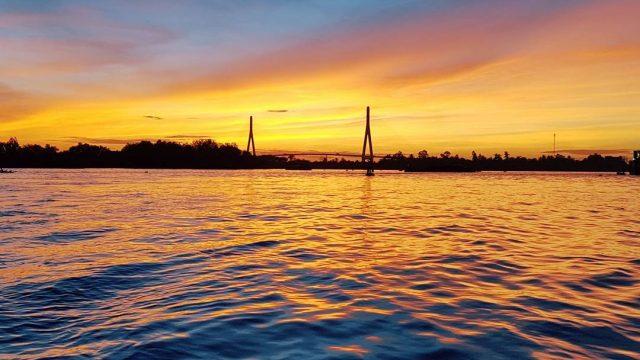 Ngắm nhìn hoàng hôn chiều dần buông, cây cầu dài cong cong, ẩn mình trên nền bầu trời xanh thẳm