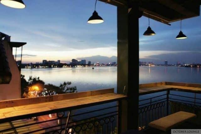 Dãy bàn ngoài ban công tầng 4 với view nhìn thẳng ra Hồ Tây dưới ánh đèn vàng lung linh