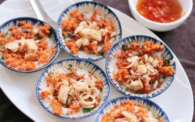 Những chiếc bánh màu trắng được rắc ruốc tôm hay ruốc bông cá ngừ, đậu phộng, lá hẹ thái nhỏ phía trên, vài mẩu bánh mì giòn tan (Ảnh ST)